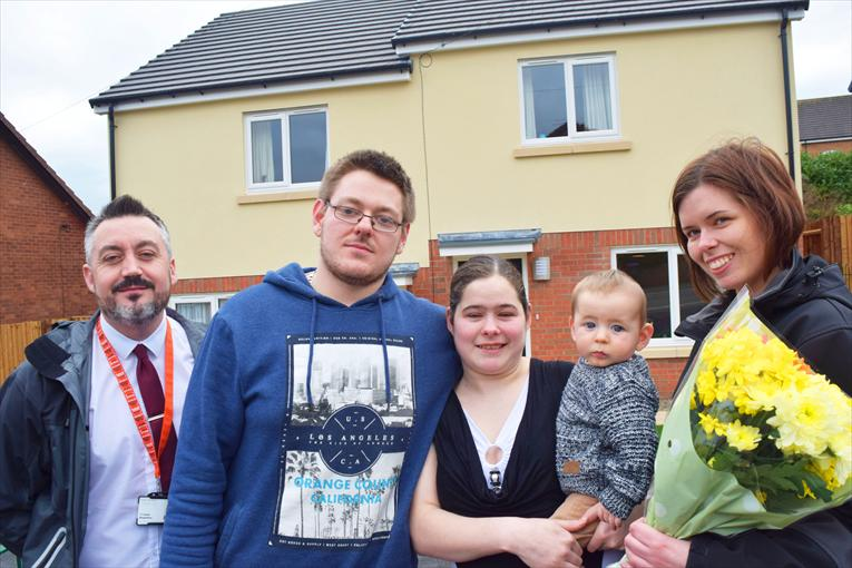 Young family with Trust staff at their new home